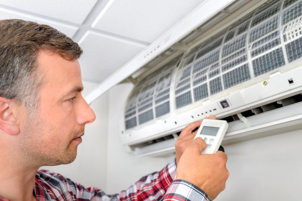 Engineer changing the filter on an air conditioning unit