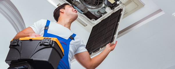 Air conditioning engineer carry out a maintenance check