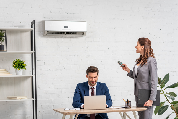 Woman controlling wall mount air conditioning system in a office