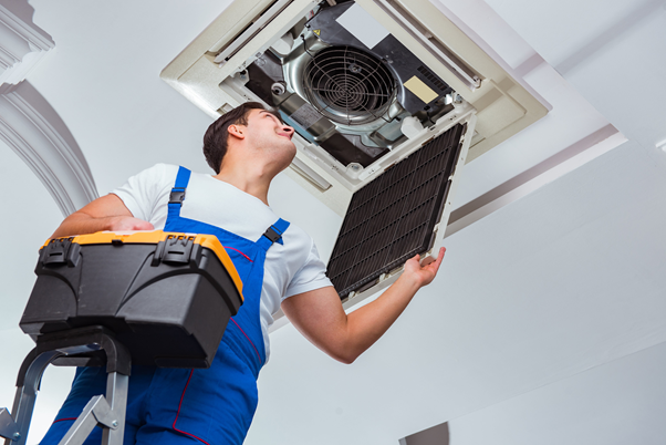 Air conditioning engineer carrying out maintenance and servicing to a ceiling aircon system